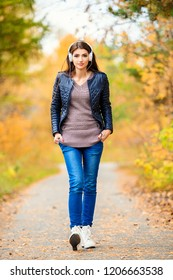 A beautiful young woman walking in an autumn forest along the path and listening to music. Lifestyle, autumn fashion, beauty.