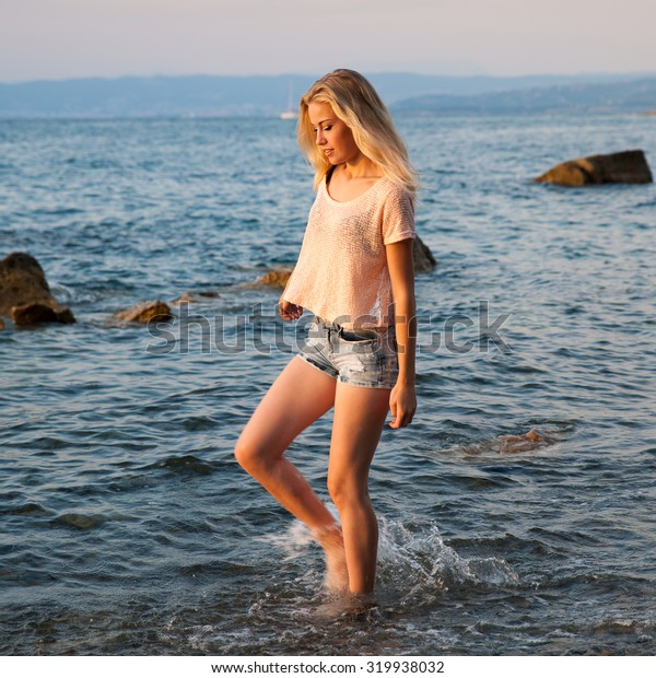 Beautiful young woman walking in the beach at sunset