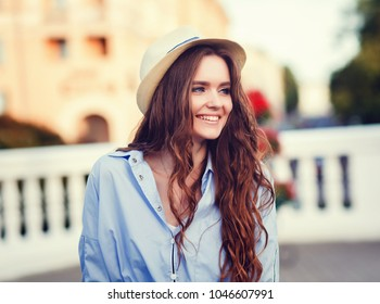 Beautiful young woman walking in the city. Fashion style