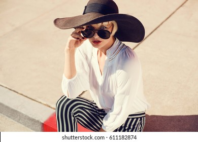 Beautiful young woman walking in a city next to red brick wall in white blouse, striped pants , hat, sunglasses. Fashion summer photo. Big smile