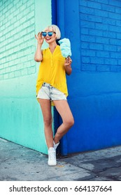 Beautiful young woman walking in a city next to blue wall in jeans shorts, yellow blouse and sunglasses holding cotton candy. Fashion summer photo. Big smile