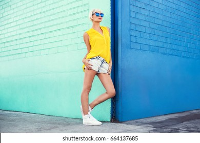 Beautiful young woman walking in a city next to blue wall in jeans shorts, yellow blouse and sunglasses. Fashion summer photo. Big smile