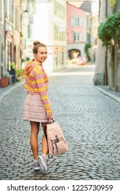 Beautiful young woman walking down the street, wearing yellow and pink stripe sweatshirt, skirt, holding backpack, looking back over the shoulder