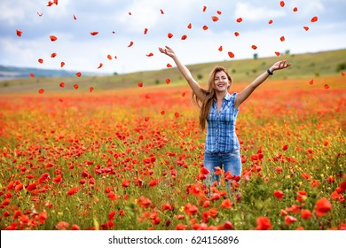Beautiful young woman walking in a field of poppies