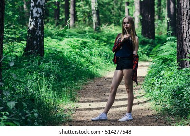 A beautiful young woman walking in the forest on the road