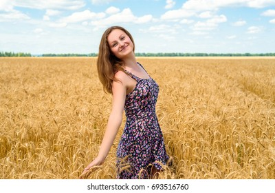 Beautiful young woman walking in golden wheat field with cloudy blue sky background, free space. Liberty, peace of mind concept. Girl in spikes of ripe wheat field under blue sky