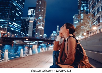 beautiful young woman walking near Chicago river at night