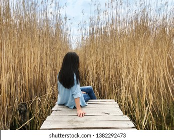 Beautiful Young Woman Walking on a Wooden Bridge in a Reed Marsh .People and Nature