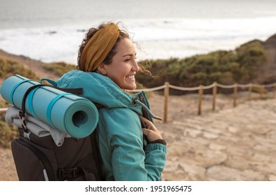 Beautiful young woman walking on a path alonside the coastline - Sportive woman carrying a yoga mat on top of her backpack, on a hike on the mountain - Shutterstock ID 1951965475