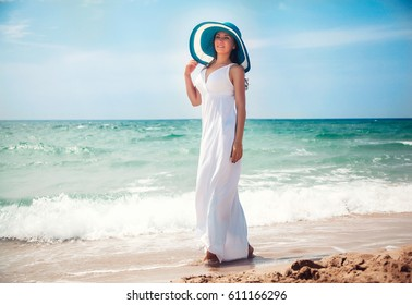 Beautiful young woman walking on the beach in long white dress and fashion hat. Holiday concept.
