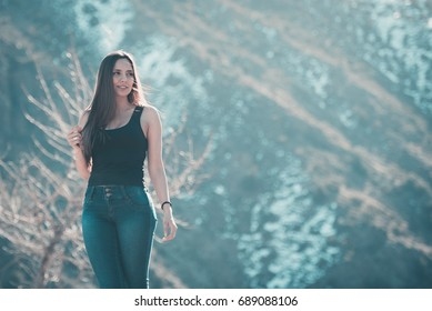 Beautiful young woman walking on the mountain with a winter background