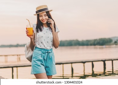 Beautiful young woman walking with phone and orange drink on pier at sunset in summer.