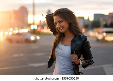 Beautiful young woman walking in the street with defocused city lights at the background. Hipster girl enjoying nightlife, fashion girl in leather jacket standing on street with city illumination