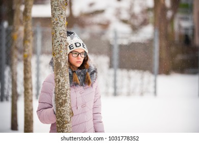 Beautiful young woman walking in winter forest outdoor