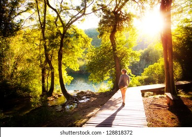 Beautiful young woman walks in Krka national park in Croatia at sunset