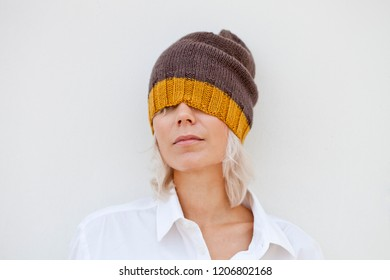 Beautiful young woman in warm brown beanie wool knitted hat.