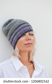Beautiful young woman in warm grey beanie wool knitted hat.