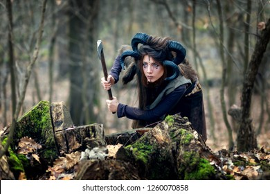 Beautiful young woman warrior with blue eyes and specific makeup wearing ram horns and fur collar hiding behind stumps in forest, stalking and ready to attack with ax.