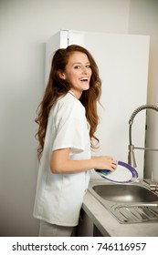 Beautiful young woman wash dishes in the kitchen.