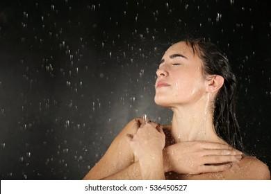 Beautiful young woman washing body in a shower