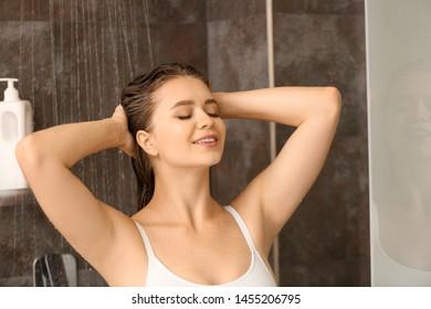 Beautiful young woman washing hair in shower