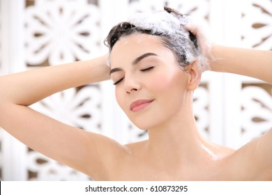Beautiful young woman washing hair in bathroom at home