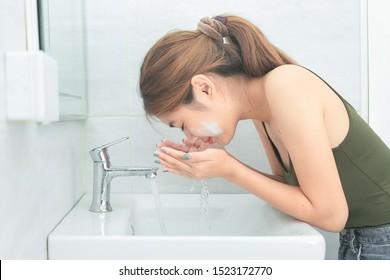 Beautiful young woman washing her face splashing water in a bathroom.
