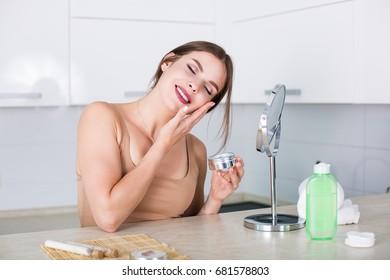 Beautiful young woman washing up her face
