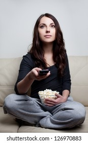 Beautiful young woman watching television