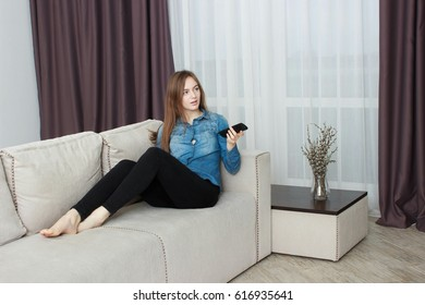 Beautiful young woman watching television sitting surrounded by cushions on a comfortable sofa with the remote control in her hand.