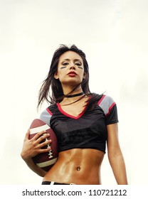 Beautiful young woman wearing American football top holding ball