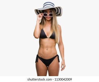 Beautiful young woman wearing bikini, sunglasses and hat skeptic and nervous, frowning upset because of problem. Negative person.
