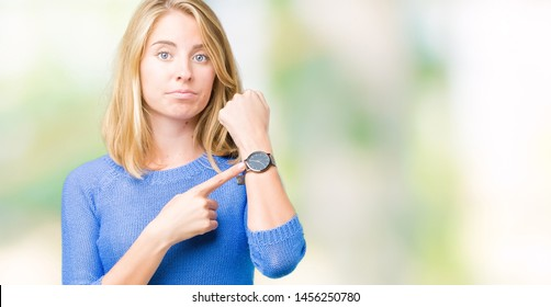Beautiful young woman wearing blue sweater over isolated background In hurry pointing to watch time, impatience, upset and angry for deadline delay