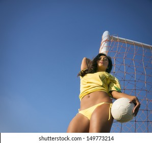 Beautiful young woman wearing Brazil soccer top and bikini bottoms holding football with goal net and blue sky.