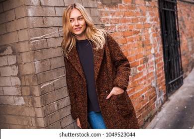 Beautiful young woman wearing casual clothes stands on a street waiting for a meeting. Standing in front of old brick wall looking aside