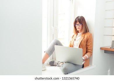 Beautiful young woman wearing casual in eyeglasses working by laptop in the office
