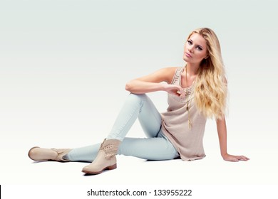 beautiful young woman wearing casual clothes and boots sitting on white background
