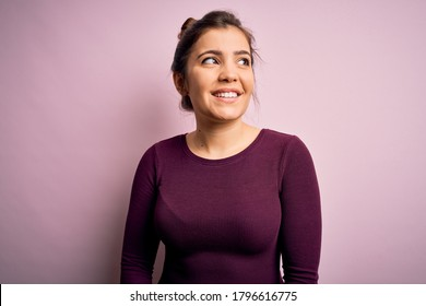 Beautiful young woman wearing casual bun hairstyle over pink isolated background looking away to side with smile on face, natural expression. Laughing confident.