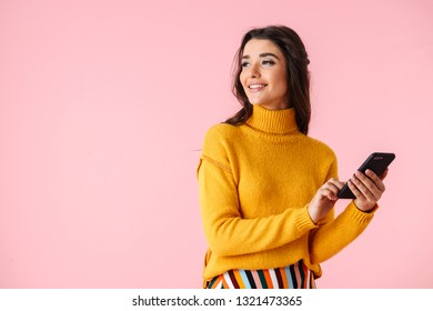Beautiful young woman wearing colorful clothes standing isolated over pink background, using mobile phone