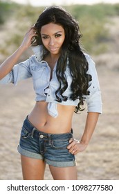 Beautiful young woman wearing denim top and shorts in Arizona desert location.