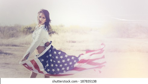 Beautiful young woman wearing denim shirt holding American flag in the open desert.  Image contains scratches and noise as part of the style.