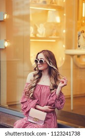 Beautiful young woman wearing dress and sitting in city
