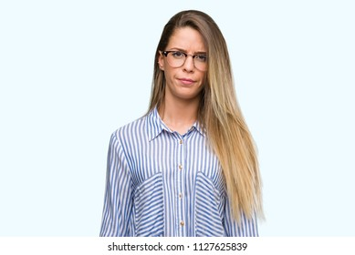 Beautiful young woman wearing elegant shirt and glasses skeptic and nervous, frowning upset because of problem. Negative person.