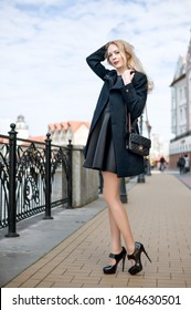 Beautiful young woman wearing fashion black dress walking in the street of the city. Coat and high heeled shoes