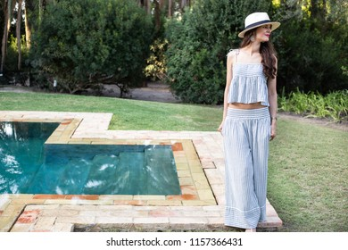 Beautiful young woman wearing fashionable summer outfit standing near pool and green trees. Fashion model photo.
