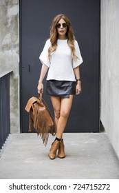 Beautiful young woman wearing fashionable clothes walking on the street