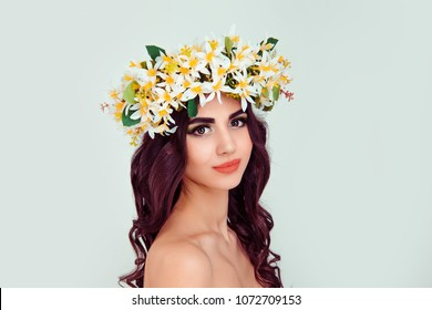 Beautiful young woman wearing floral headband tiara crown isolated light green background. White yellow blossom wreath of flowers on head looking at you smiling slightly daydreaming cute gorgeous girl