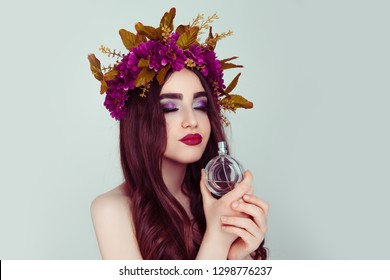 Beautiful young woman wearing floral headband isolated light green background burgundy daisy wreath of flowers on head eyes closed holding smelling perfume bottle enjoying new aroma cute brunette girl