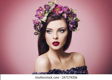 beautiful young woman wearing floral headband and bright makeup