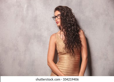 beautiful young woman wearing glasses pose looking away with her hands down